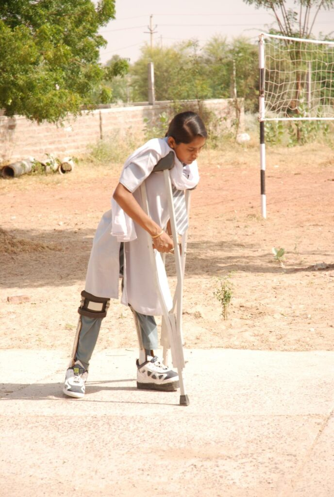 A girl in calipers and on crutches makes her way to the playground.