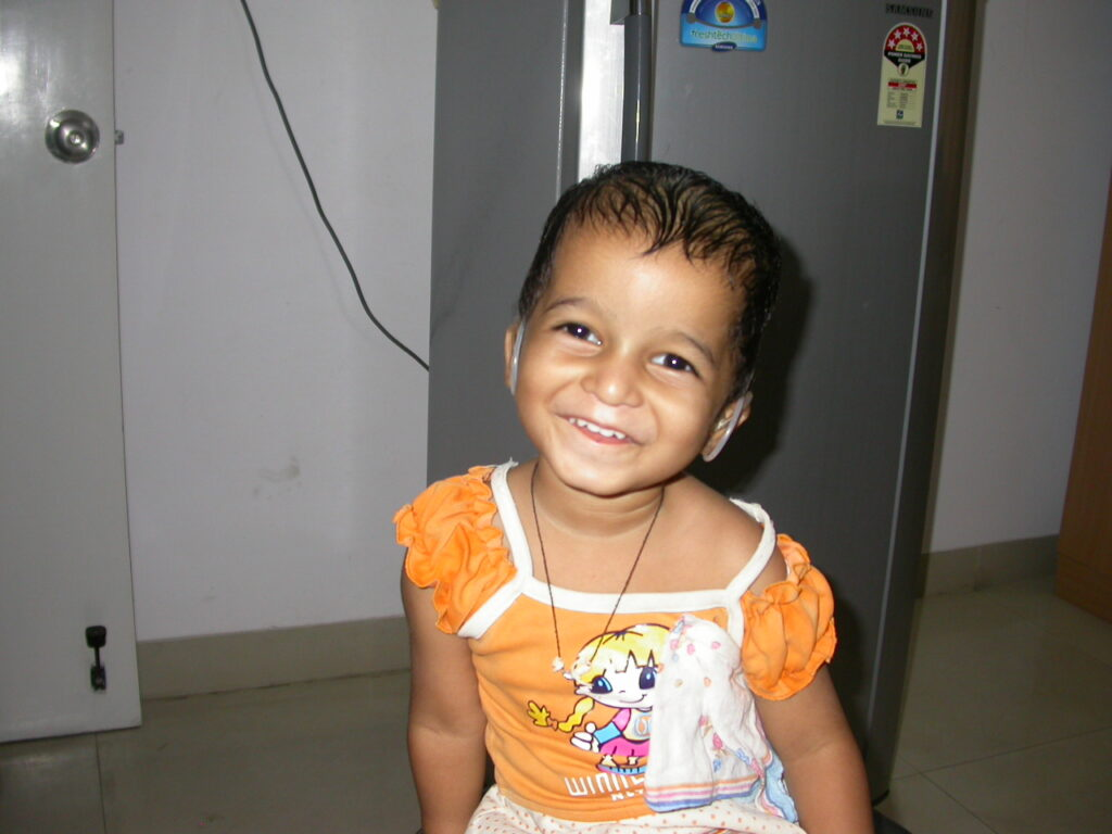 A young girls smiles as she perceives sound for the first time with her new hearing aids