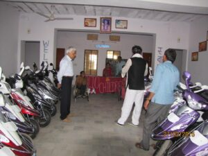 Arun Sangave, Treasurer, PACINC (USA) inspects handicapped-modified scooters donated for college-bound students.