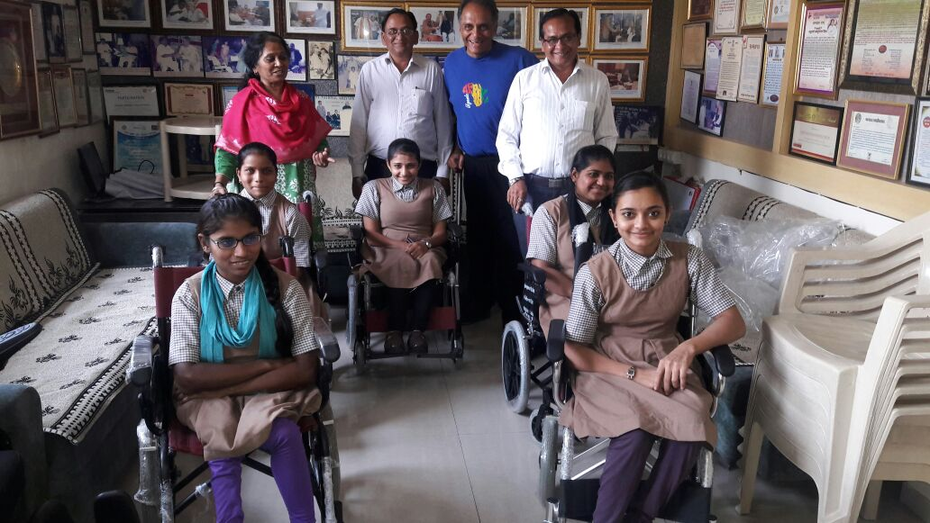 Girls beaming after receiving wheelchairs