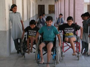 Girls enjoying racing their new wheelchairs in the school corridors