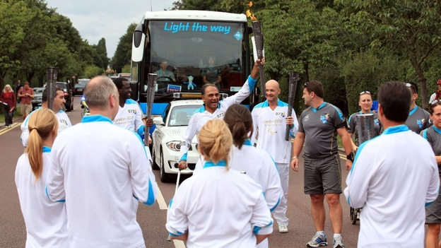 PACINC Co-founder Arun Patel holds up the olympic torch before London Paraolympics