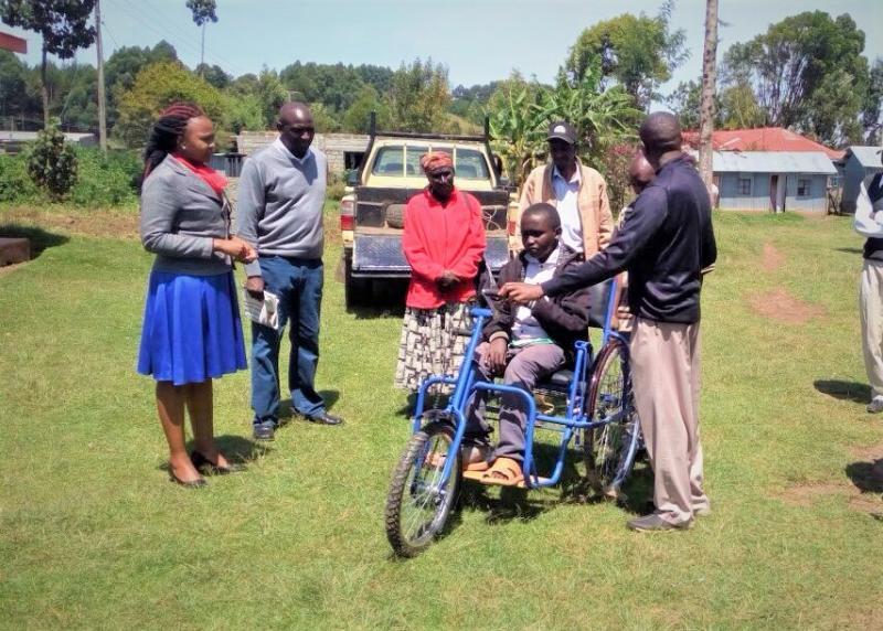 A boy and his family receiving a wheelchair.