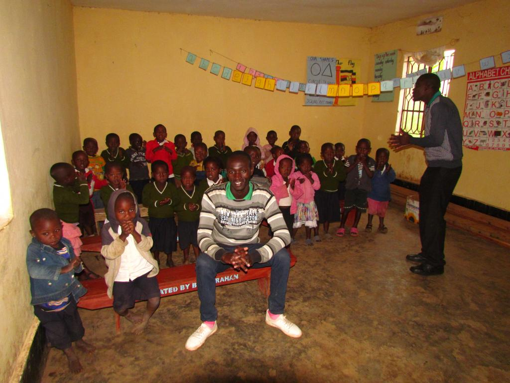 Titus Arinaiwe, founder of KOCC, with children in one of the classrooms
